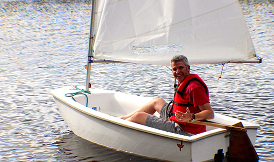 Image Director Tommy on a boat at Camp Granite Lake